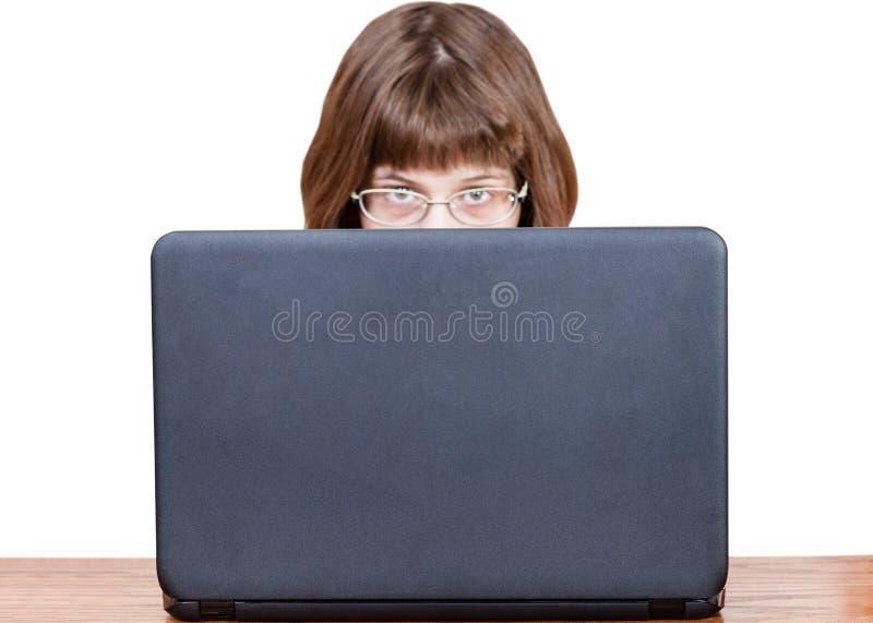 Девушка с зрелищами рассматривает крышка компьтер-книжки стоковое изображение