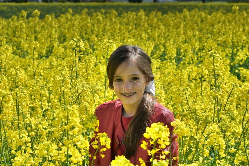 Девушка с зубоврачебными расчалками в поле с желтыми цветками стоковая фотография