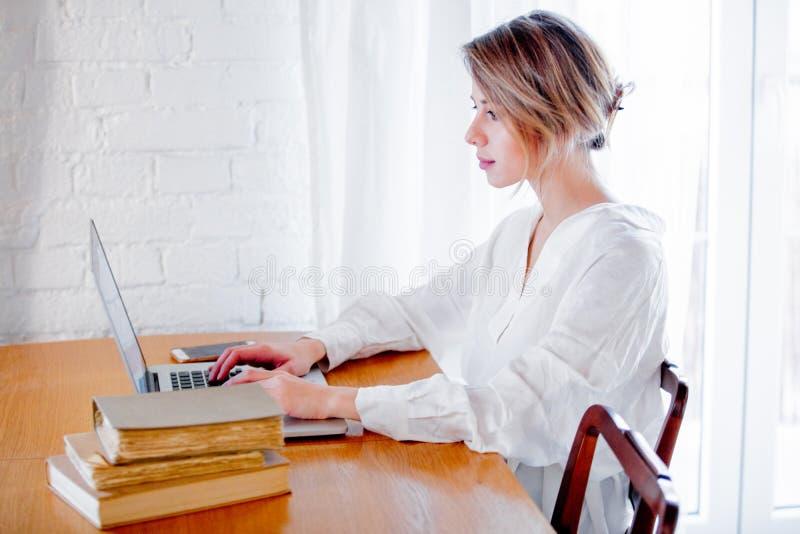 Девушка с книгами и ноутбуком стоковые фото