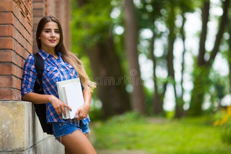 Девушка с книгой в университете стоковые фотографии rf