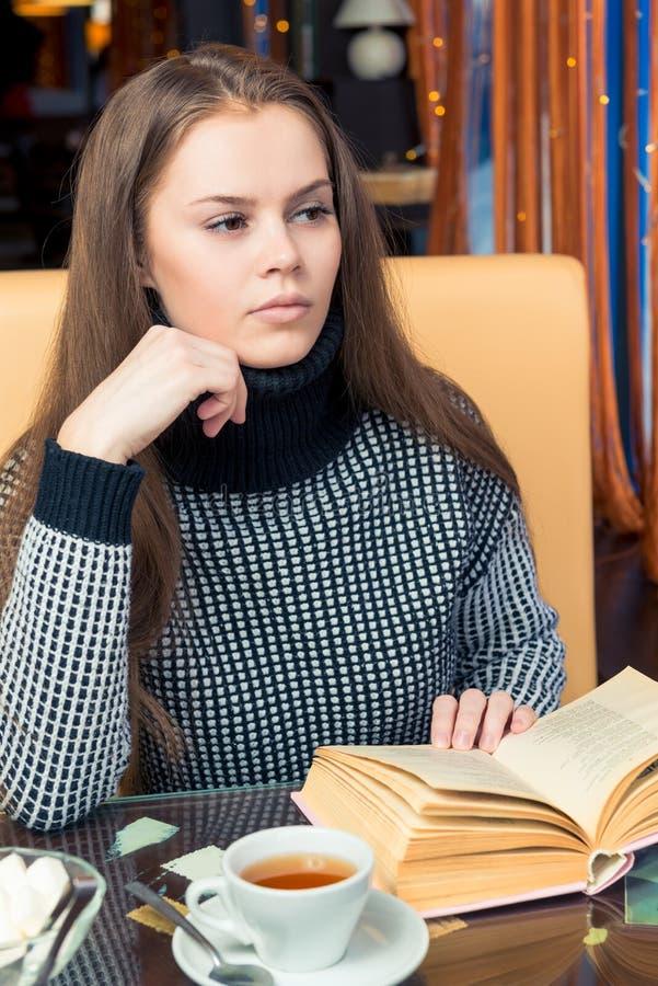 Девушка с книгой обдумала на таблице в кафе, смотрит вне стоковые фото