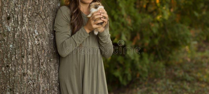 Девушка с коричневыми волосами держит малый коричневый цвет с белым кроликом в руках ` s детей на зеленой предпосылке ребенок дер стоковые изображения