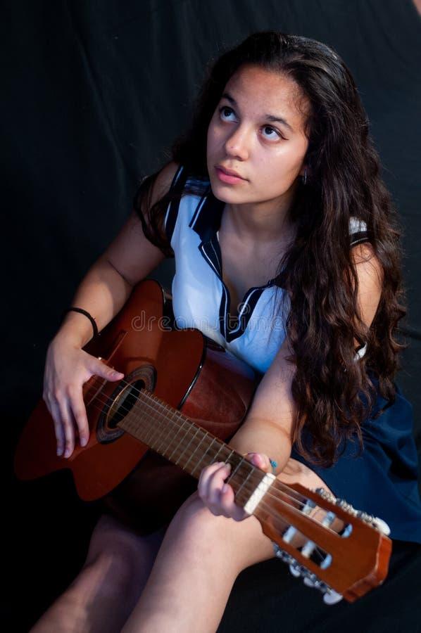 Девушка с коричневыми волосами, усаживанием, пока усмехающся пока играющ гитару Я смотрю изумил на камере На черной предпосылке стоковая фотография