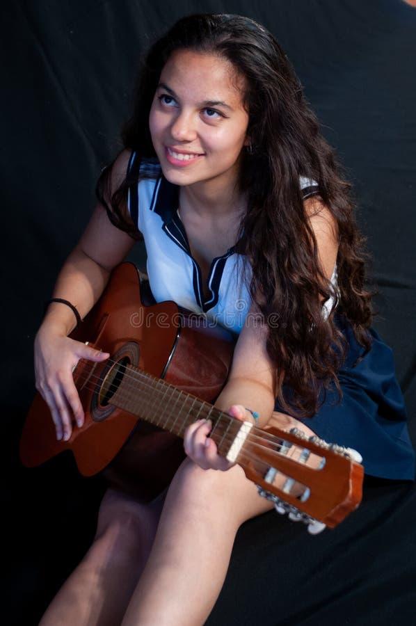 Девушка с коричневыми волосами, усаживанием, пока усмехающся пока играющ гитару Я смотрю изумил на камере На черной предпосылке стоковое изображение rf