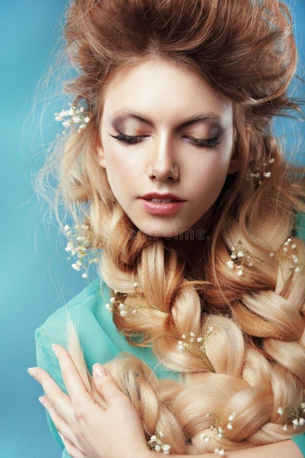 Девушка с косичкой и переплетаннсяыми цветками стоковая фотография