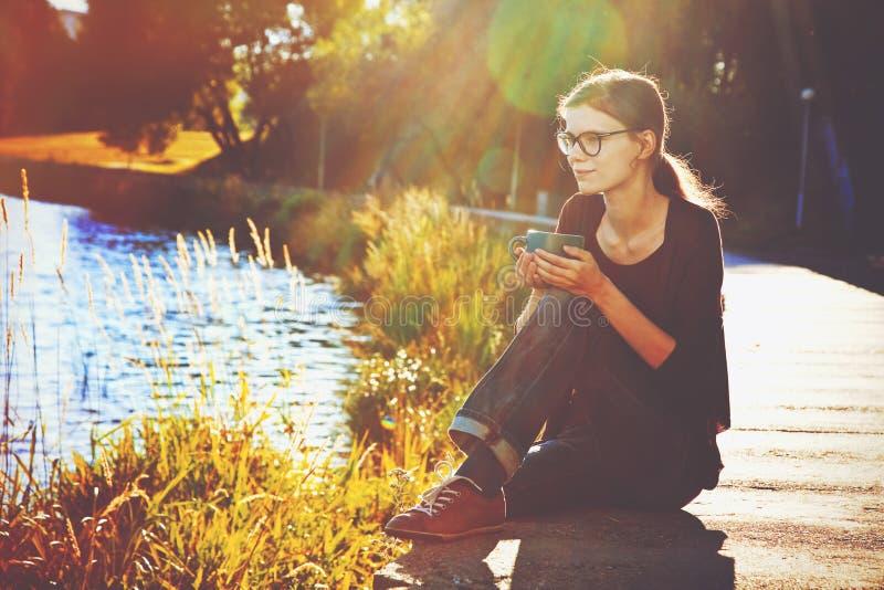 Девушка с кофейной чашкой около реки стоковая фотография