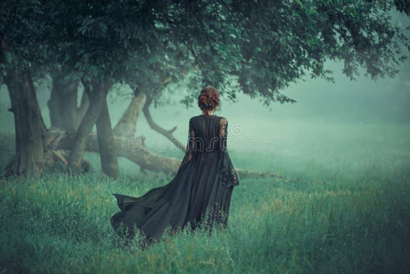 Девушка с красными волосами идя вперед от темного леса, нося длинного черного платья с трейлером который развевает в ветре стоковые фотографии rf