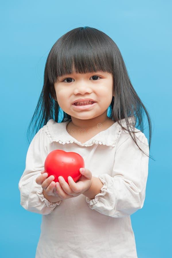 Девушка, с красным сердцем в руке стоковое изображение rf