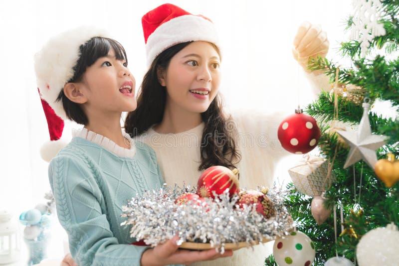 Download Девушка с мамой украшает рождественскую елку Стоковое Изображение - изображение: 104302873