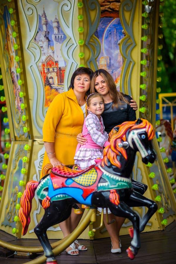 Девушка с матерью и bubashka на каруселях стоковые фото