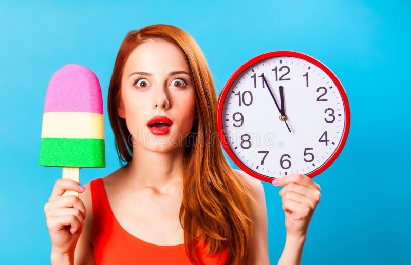 Девушка с мороженым игрушки и огромными часами стоковое фото