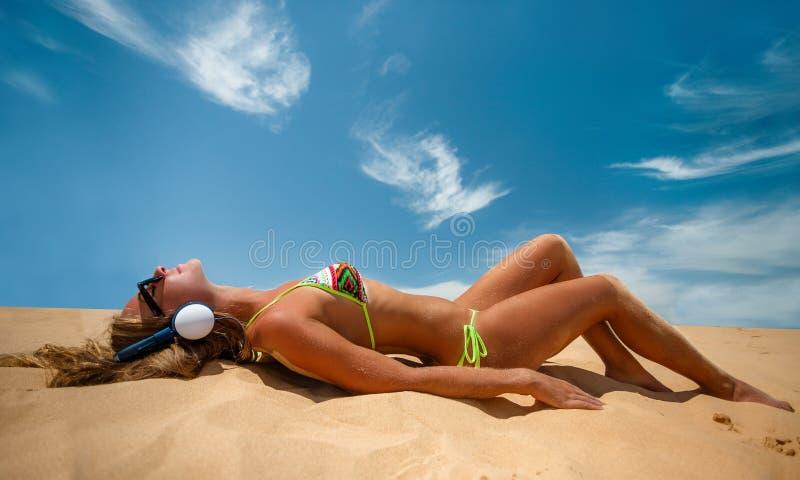 Девушка с наушниками загорая в летнем времени стоковое изображение