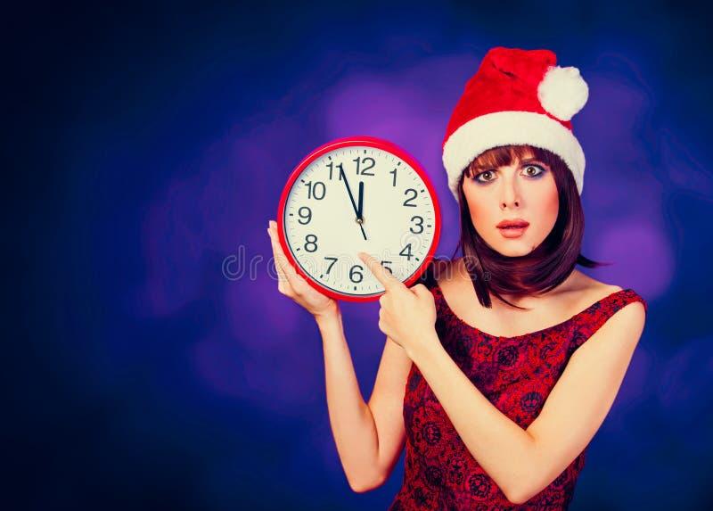 Девушка с огромными часами и шляпой стоковая фотография