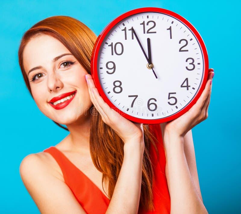 Девушка с огромными часами на голубой предпосылке стоковое изображение