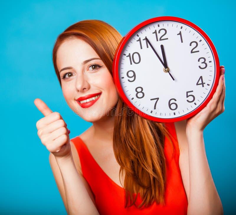 Девушка с огромными часами на голубой предпосылке стоковое изображение rf