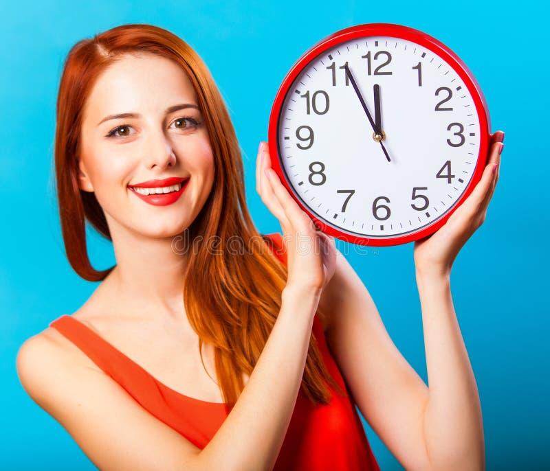 Девушка с огромными часами на голубой предпосылке стоковые фото