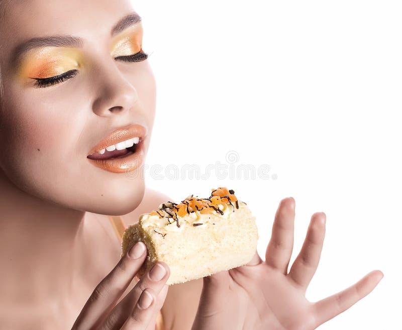 Девушка с очень вкусным оранжевым пралине стоковое фото