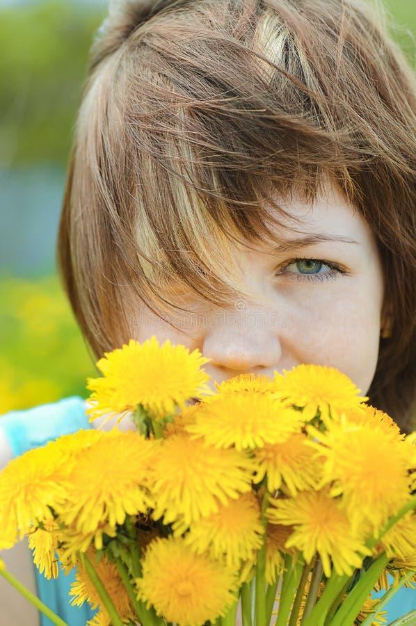Девушка с одуванчиками стоковая фотография
