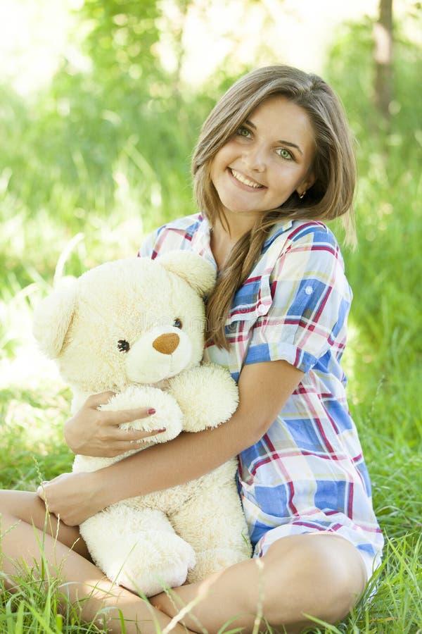 Девушка с плюшевым медвежонком в парке стоковые изображения