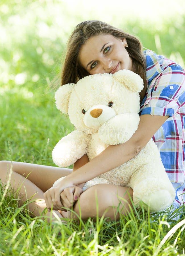 Девушка с плюшевым медвежонком в парке стоковое изображение rf