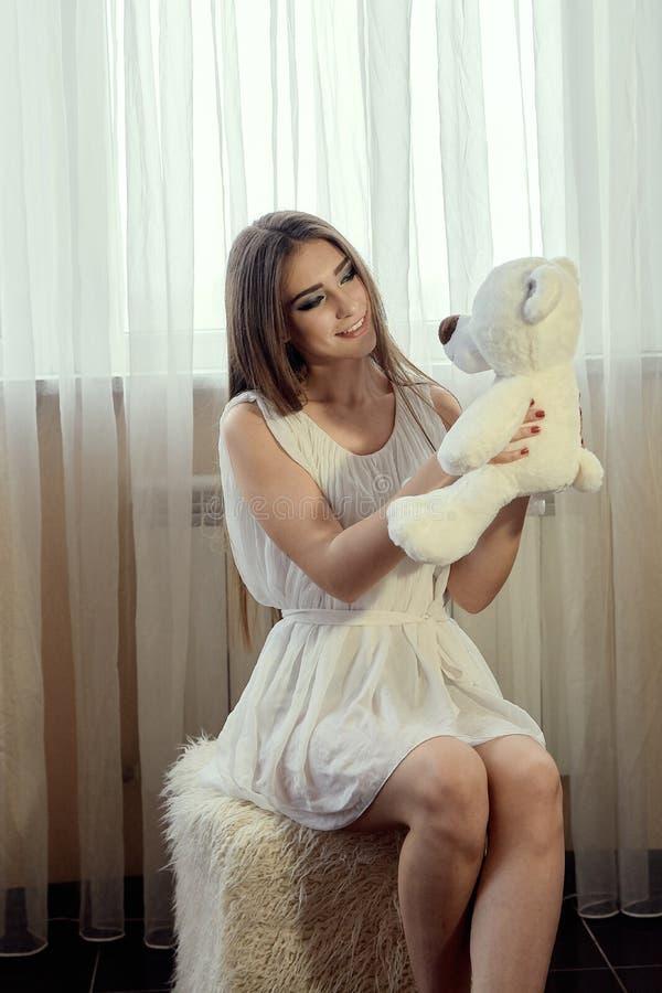 Девушка с плюшевым мишкой для дизайна образа жизни Молодая кавказская модель красивейшая женщина стороны стоковое изображение