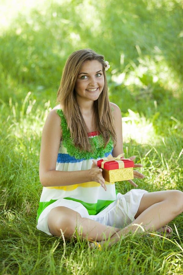 Девушка с подарком в парке на зеленой траве. стоковая фотография