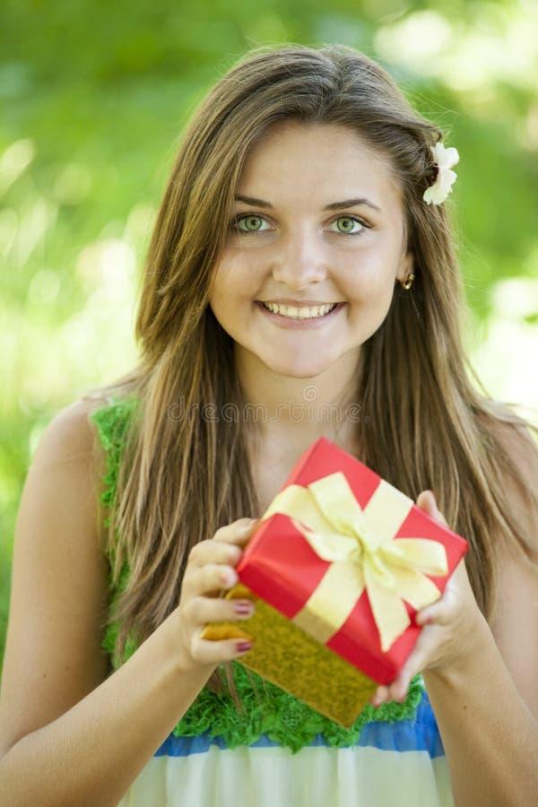 Девушка с подарком в парке стоковое фото