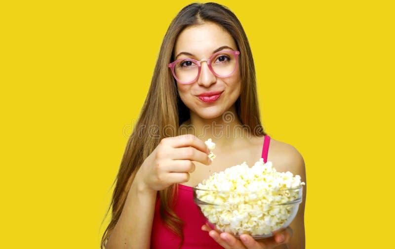 Девушка с положительной эмоцией держа попкорн и смотря фильм комедии изолированная на желтом портрете студии предпосылки стоковое фото