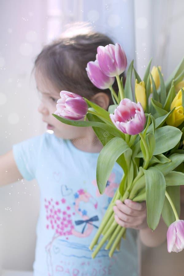 Девушка с примечанием цветков весны НА уютном доме в живущей комнате окном красит различные тюльпаны Подарок на a стоковое фото