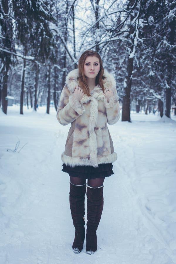 Девушка с пропуская волосами в бежевой меховой шыбе и коричневые стойки ботинок против фона леса зимы стоковая фотография