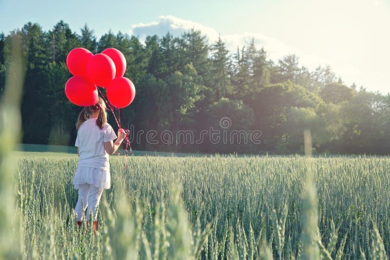 Девушка с пуком красных воздушных шаров стоковое фото rf