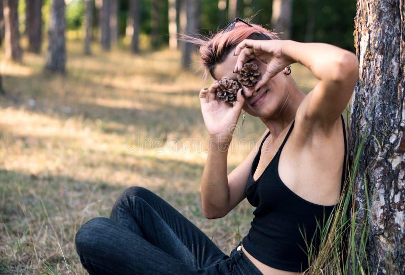 Девушка с рему Девушка Joying молодой милой пригонки панковская в черной верхней части с розовыми волосами в сосновом лесе на вре стоковые изображения rf
