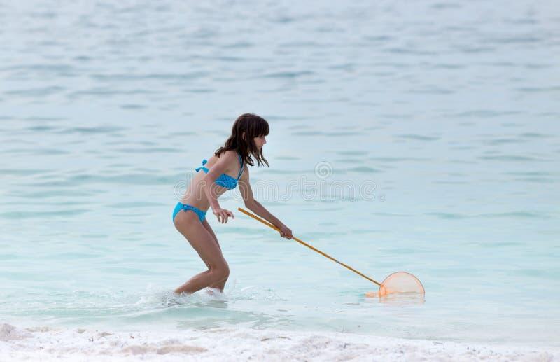 Девушка с рыболовной сетью на море стоковые фотографии rf