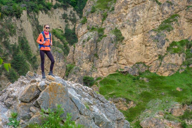 Девушка с рюкзаком в горах стоковые изображения