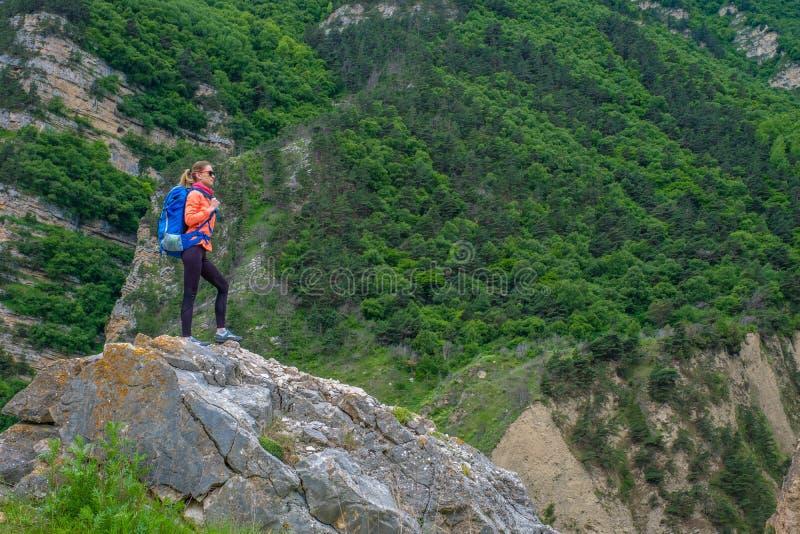 Девушка с рюкзаком в горах стоковое изображение