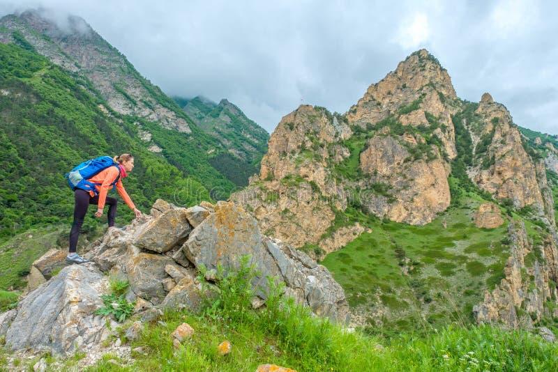 Девушка с рюкзаком в горах стоковые изображения rf