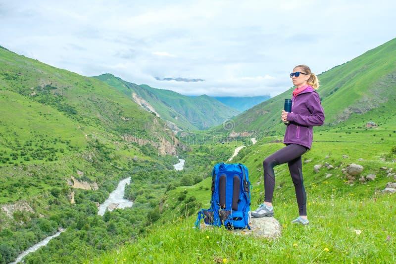 Девушка с рюкзаком в горах стоковое фото