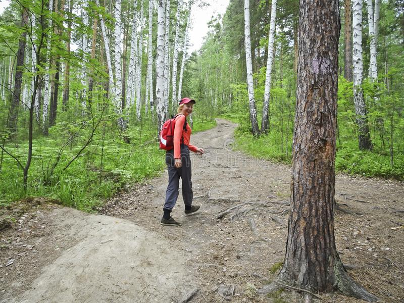 Девушка с рюкзаком идет вдоль пути леса и смотрит назад стоковое изображение