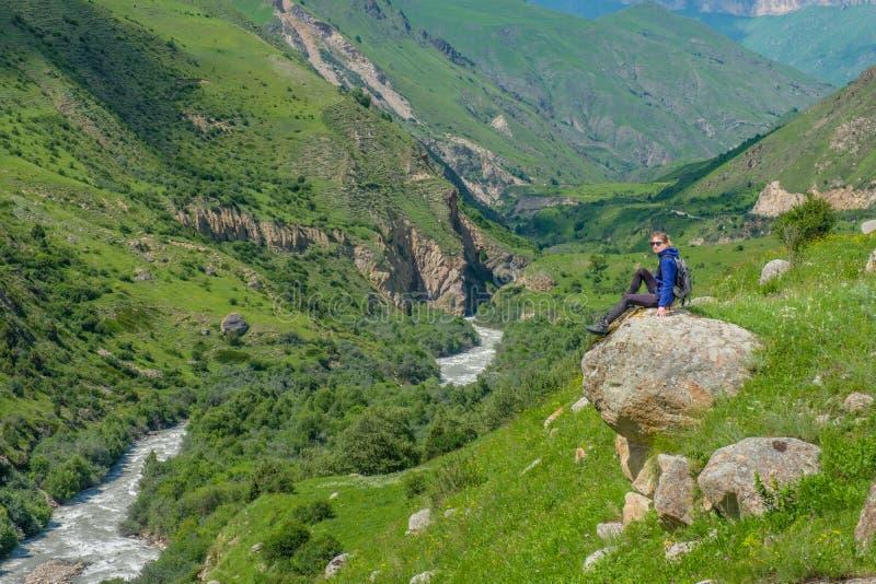 Девушка с рюкзаком отдыхает в горах Панорама гор Кавказа стоковое фото