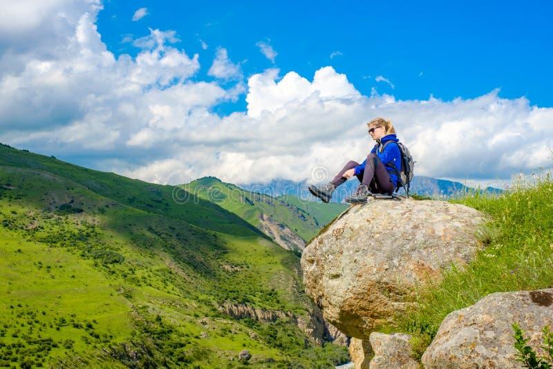 Девушка с рюкзаком отдыхает в горах Панорама гор Кавказа стоковое фото rf
