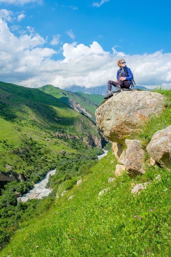 Девушка с рюкзаком отдыхает в горах Панорама гор Кавказа стоковое изображение