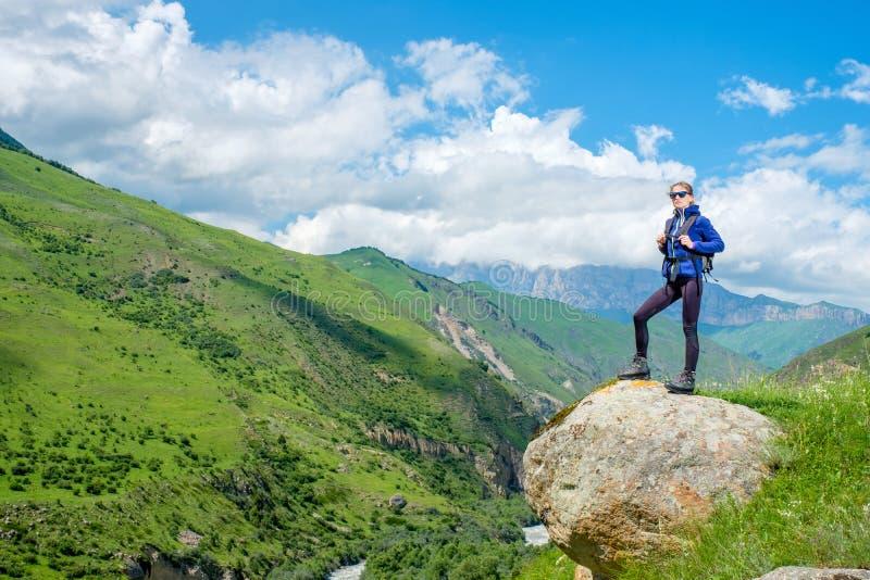 Девушка с рюкзаком отдыхает в горах Панорама гор Кавказа стоковые изображения rf