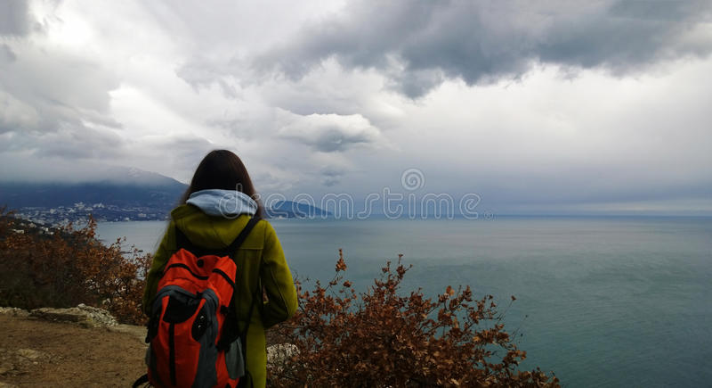 Девушка с рюкзаком смотрит в расстояние в море и горах Фокус на заднем плане стоковое изображение rf