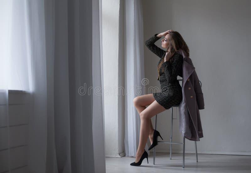 Девушка с серым пальто сидит на стуле смотря из окна стоковое фото rf