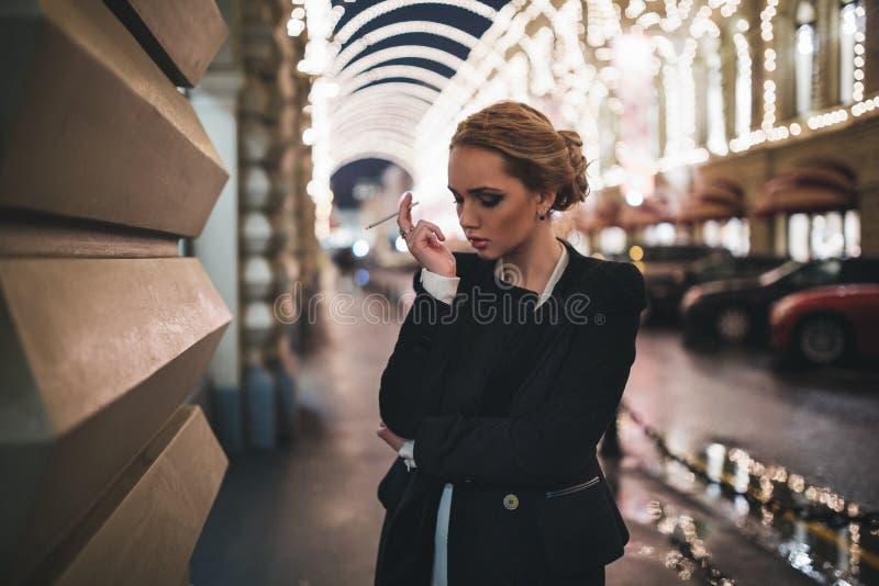 Девушка с сигаретой в его руке против стоковые фотографии rf