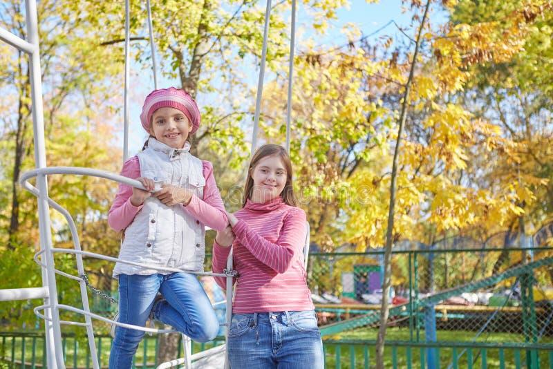 Девушка с Синдромом Дауна и маленькой девочкой в парке осени стоковое изображение rf