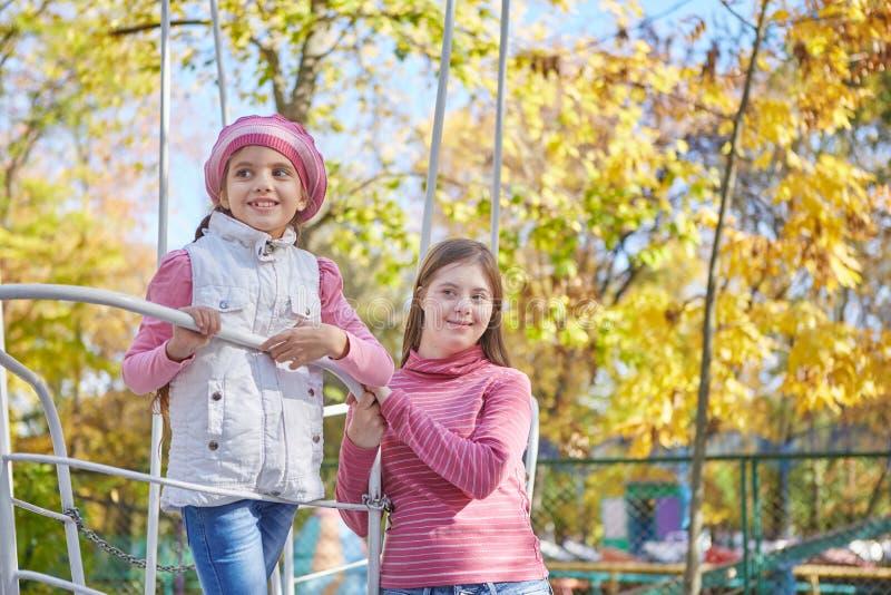 Девушка с Синдромом Дауна и маленькой девочкой в парке осени стоковое изображение