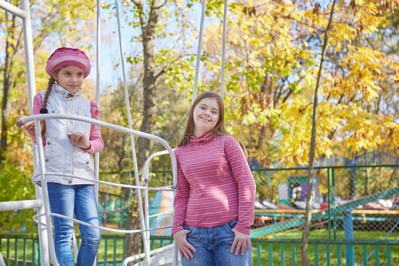 Девушка с Синдромом Дауна и маленькой девочкой в парке осени стоковые изображения