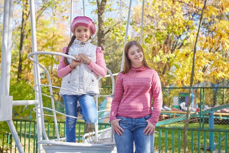 Девушка с Синдромом Дауна и маленькой девочкой в парке осени стоковые фотографии rf