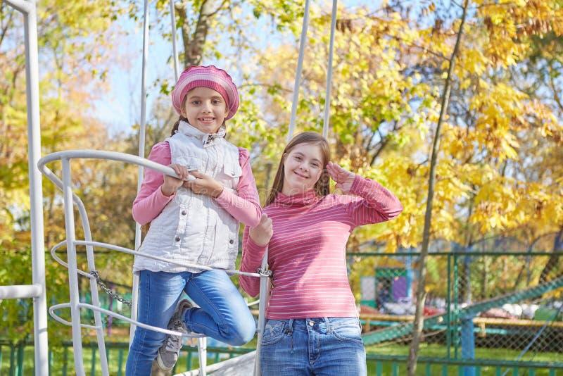 Девушка с Синдромом Дауна и маленькой девочкой в парке осени стоковая фотография